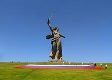 活动家在俄罗斯的天Mamaev小山的松开一面大俄国旗子在伏尔加格勒 免版税库存照片
