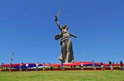 活动家松开一面大俄国旗子在俄罗斯的天在祖国电话的纪念碑的脚在Mamaev小山的在伏尔加格勒 免版税库存图片