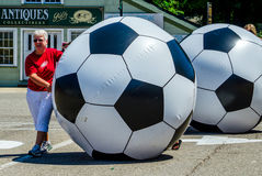 滚动巨型足球的妇女 图库摄影
