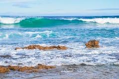 滚动往岩石、完善的蓝色和水色海洋的波浪浇灌,岩石在岸,在天空的高层云 库存照片