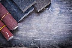 滚动擦亮的纸铺沙的海绵在葡萄酒木头板 免版税库存照片