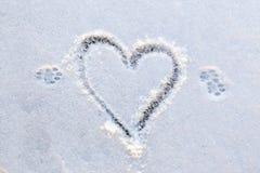 动物` s脚在第一雪打印和心脏形状 免版税库存照片