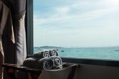 滚动的毛巾在有海scape的屋子里 图库摄影