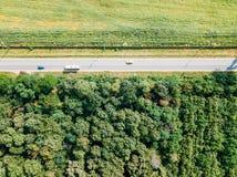 移动的汽车空中寄生虫视图在乡下公路的有森林和农业庄稼领域的 库存图片