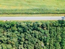 移动的汽车空中寄生虫视图在乡下公路的有森林和农业庄稼领域的 免版税库存照片