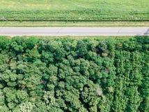 移动的汽车空中寄生虫视图在乡下公路的有森林和农业庄稼领域的 库存照片
