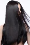 移动的美丽的深色的女孩与一根完全光滑的头发和经典构成 秀丽表面 免版税库存照片