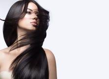 移动的美丽的深色的女孩与一根完全光滑的头发和经典构成 秀丽表面 图库摄影