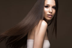 移动的美丽的深色的女孩与一根完全光滑的头发和经典构成 秀丽表面 库存图片