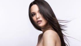 移动的美丽的深色的女孩与一根完全光滑的头发和经典构成 秀丽表面 库存照片