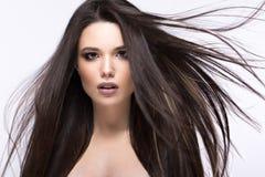 移动的美丽的深色的女孩与一根完全光滑的头发和经典构成 秀丽表面 免版税图库摄影