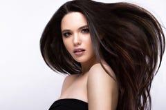 移动的美丽的深色的女孩与一根完全光滑的头发和经典构成 秀丽表面 免版税库存图片