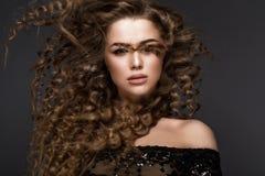 移动的美丽的深色的女孩与完全卷发和经典构成 秀丽表面 免版税库存照片