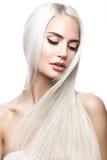 移动的美丽的白肤金发的女孩与一根完全光滑的头发和经典构成 秀丽表面 免版税库存图片