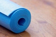 滚动的蓝色瑜伽席子 库存照片
