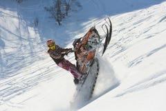 移动的雪上电车在山的冬天森林里 库存照片
