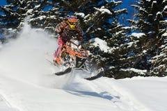 移动的雪上电车在山的冬天森林里 免版税库存图片