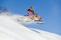 移动的雪上电车在山的冬天森林里 免版税库存照片