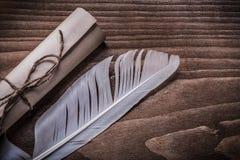 滚动葡萄酒纸羽毛在木板 免版税库存照片