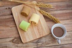 滚动酥皮点心转交在木咖啡大麦背景 图库摄影