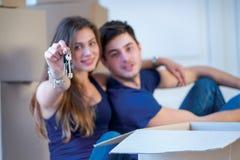 移动,修理,公寓的新的钥匙 夫妇女孩和 库存图片