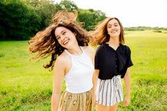 移动头发的笑的女性朋友 免版税库存图片