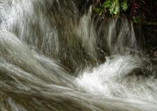 移动紧密在山的撕毁的水放出 免版税库存图片