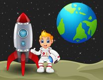 动画片拿着在月亮的宇航员男孩一只盔甲和火箭太空船与行星地球在背景中 免版税库存图片
