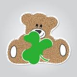 动画片-褐色,与三叶草的毛茸的微笑的熊 皇族释放例证