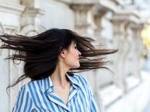 移动他的头发的美丽的深色的妇女 免版税库存照片