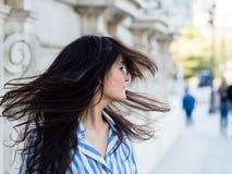 移动他的头发的美丽的深色的妇女 免版税库存图片