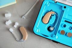 助听器和案件在灰色桌上 免版税库存照片