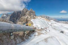 努力去做下来在台阶的人们Dachstein冰川表面  库存照片