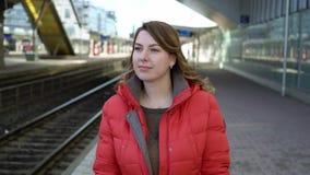 努力去做在驻地平台的年轻女人等待她的火车 股票录像