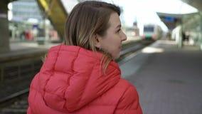 努力去做在驻地平台的年轻女人等待她的火车 影视素材
