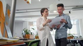 努力去做通过纸的两位年轻企业家在办公室 股票录像