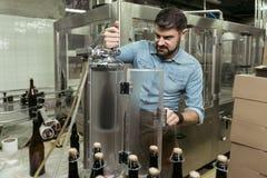 努力工作在啤酒厂的被集中的人 免版税库存照片