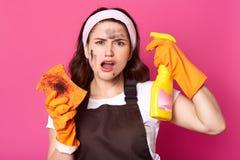 努力疲乏的女性广泛张她的嘴充满不满情绪,有肮脏的面孔和橙色海绵,拿着黄色瓶 库存图片