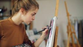 努力艺术系学生俏丽的女孩绘运作在类的美丽的图片花站立在画架附近 人是 股票录像
