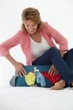 努力高级的妇女关闭手提箱 免版税库存图片