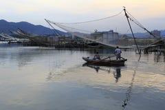 努力去做乘小船的渔夫在微明 免版税图库摄影