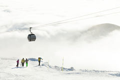 努力去做山在一个冬季体育度假区的现代长平底船在一多云天 免版税图库摄影