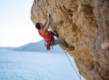 努力年轻的人攀登伸出的峭壁 免版税库存图片