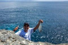 努沙Penida,印度尼西亚- 2018年3月22日:有微笑对照相机的鱼的一位渔夫 免版税库存图片