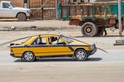 努瓦克肖特,毛里塔尼亚- 2013年10月08日:与老出租汽车运输的钢标尺的街道场面 免版税库存照片