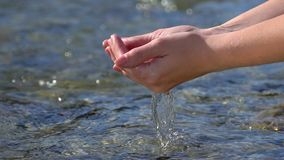 劫掠和举透明的淡水的妇女女性手在山河户外,下落入水表面 影视素材