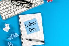 劳动节-在蓝色工作地点背景的消息 劳动节庆祝在5月1日 春天…上升了叶子,自然本底 免版税库存照片