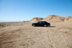 劳斯莱斯汽车在有轮胎轨道的未铺砌的路停放了 免版税库存照片