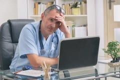 劳累过度的医生在他的办公室 图库摄影
