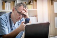 劳累过度的医生在他的办公室 免版税库存照片
